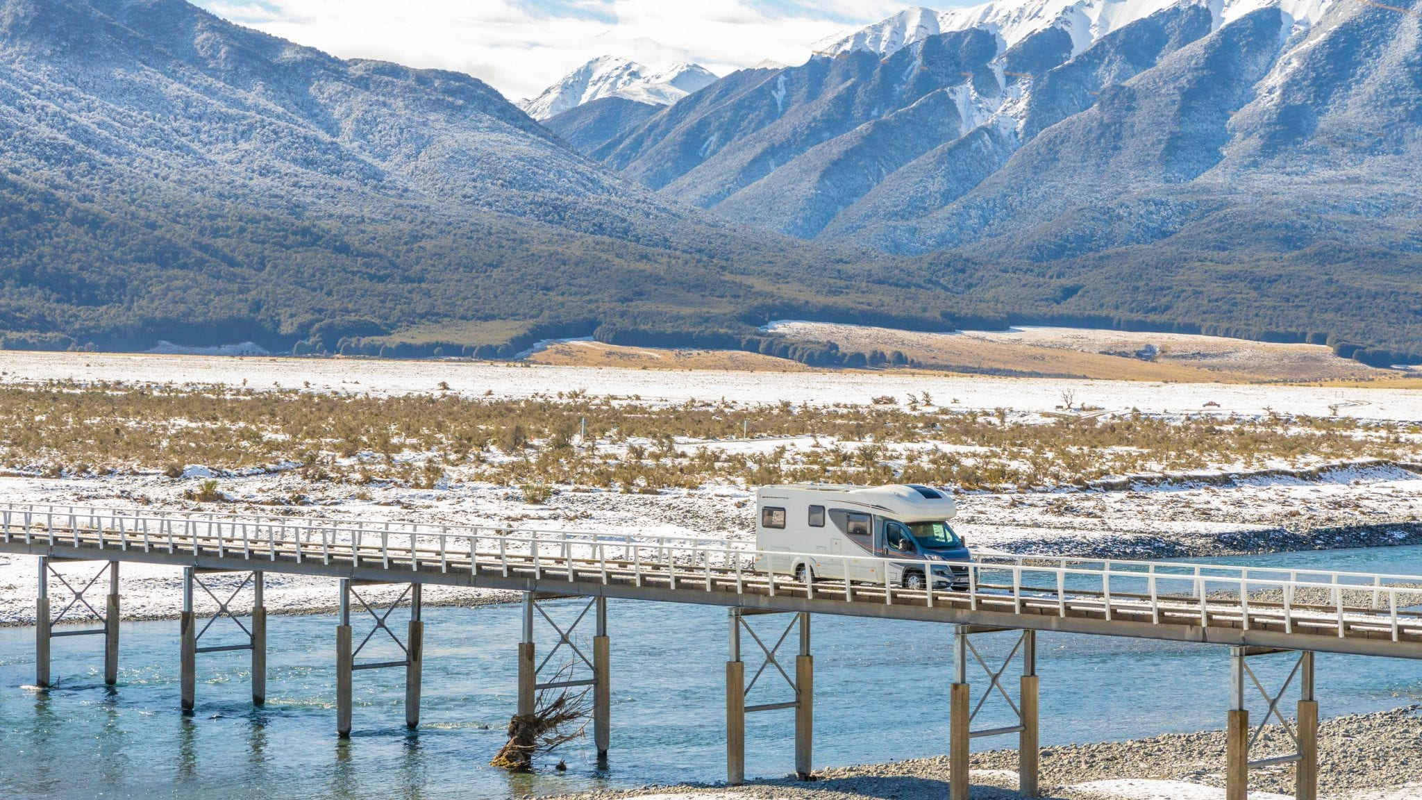 Campervan travelling across a long bridge with snow capped mountains in the background